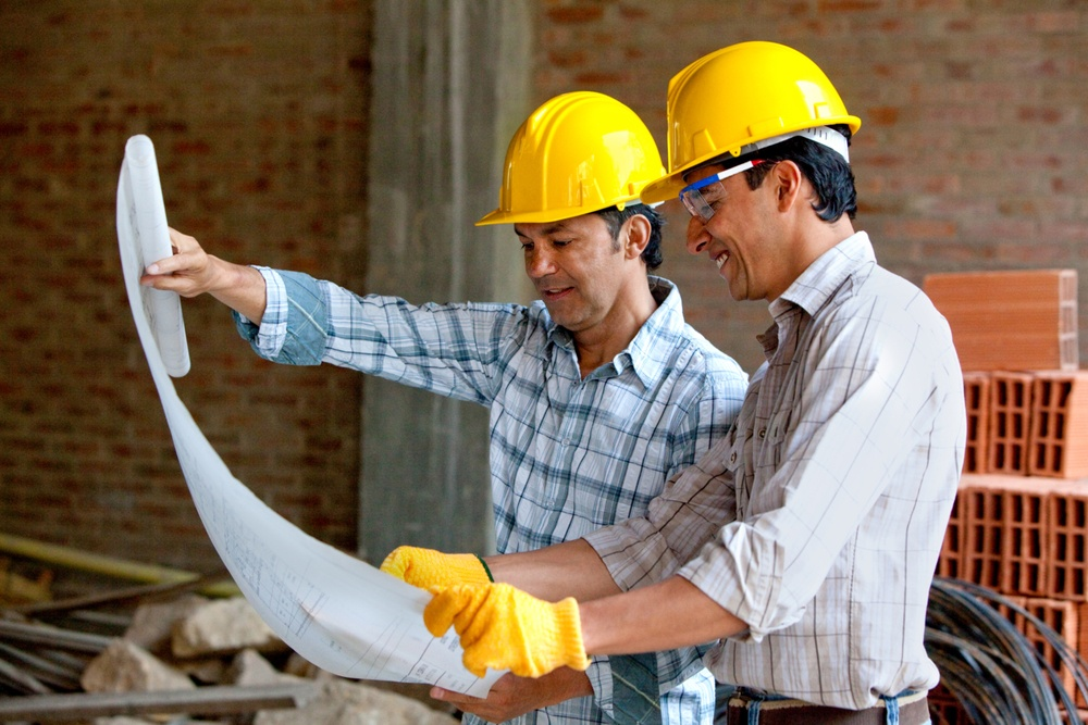 Architects at a construction site looking at blueprints