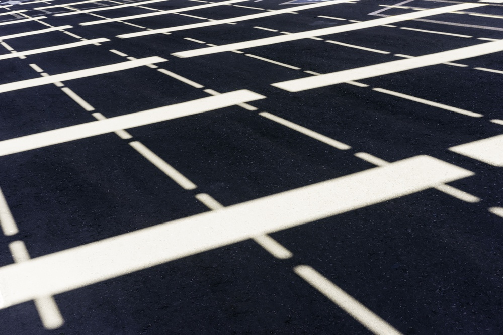 Symmetrical pattern of sunlight and white stripes on asphalt parking lot